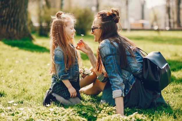 Stilvolle mutter mit langen haaren und einer jeansjacke, die mit ihrer kleinen süßen tochter spielt