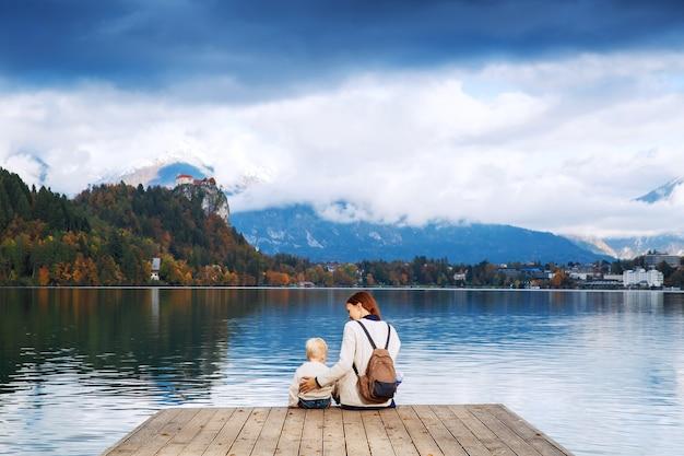 Stilvolle mutter und sohn sitzen auf einem holzsteg am bleder see slowenien