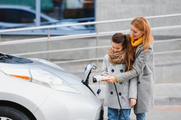 Stilvolle mutter und tochter laden ein elektroauto auf und verbringen zeit miteinander