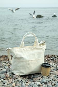 Stilvolle öko-tasche und pappbecher im freien am meer