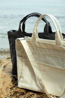 Stilvolle öko-taschen im freien auf großem seestein gegen meer