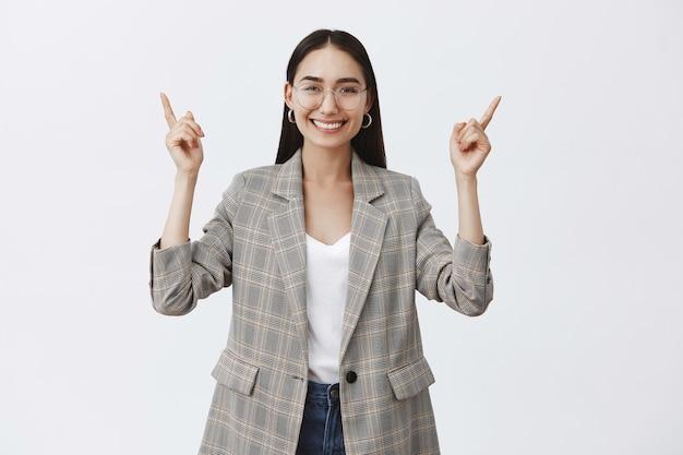 Stilvolle optimistische erwachsene unternehmerin in brille und trendiger jacke, hände heben und nach oben zeigen, während sie breit lächelt