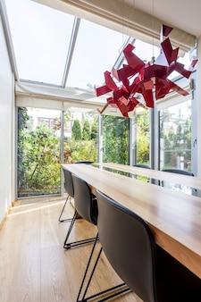 Stilvolle orangerie mit großem tisch, stühlen und dekorativem rotem kronleuchter im modernen haus