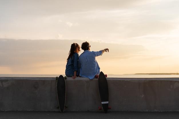 Stilvolle paar-skateboarder-mann und -frau entspannen sich und genießen den sonnenuntergang auf dem bürgersteig der küstenstraße