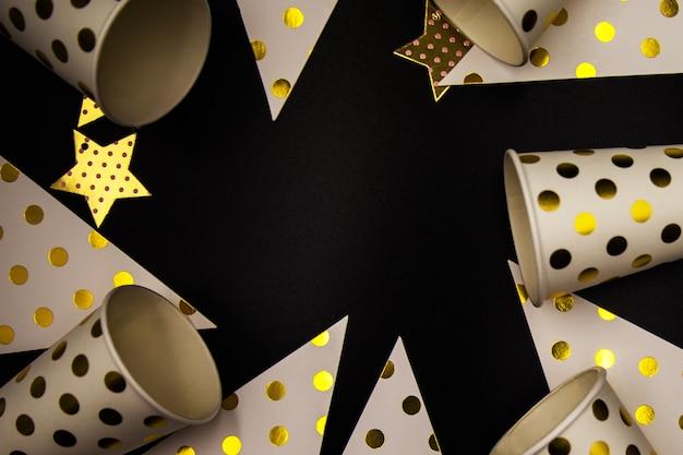 Stilvolle party goldene und weiße dekoration und pappbecher auf schwarzem hintergrund. festliches konzept mit platz für text.