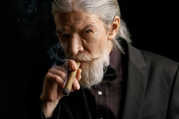 Stilvolle rauchende zigarre des alten mannes.