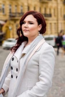 Stilvolle reife frau, die einen trendigen weißen mantel trägt und abends in der stadt spazieren geht