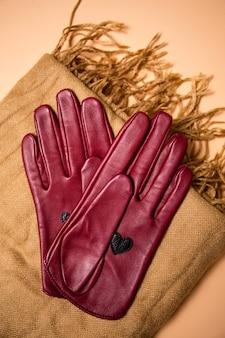 Stilvolle rote lederhandschuhe auf einem schal, draufsicht