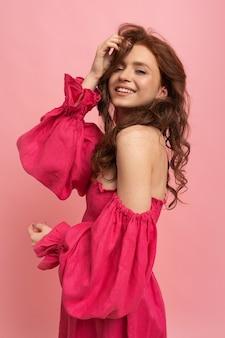 Stilvolle rothaarige frau, die mit haaren spielt und auf rosa pfandrechtkleid mit ärmeln auf rosa aufwirft
