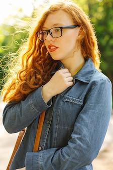 Stilvolle rothaarige junge frau in jeanshemd und brille posiert auf der straße