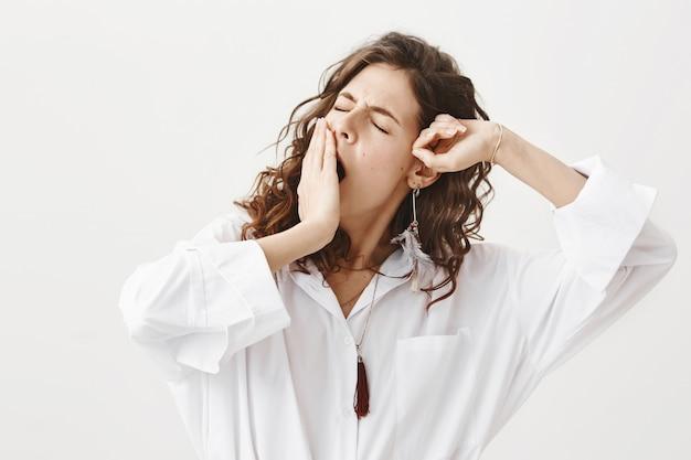 Stilvolle schläfrige frau aufwachen, gähnen und dehnen