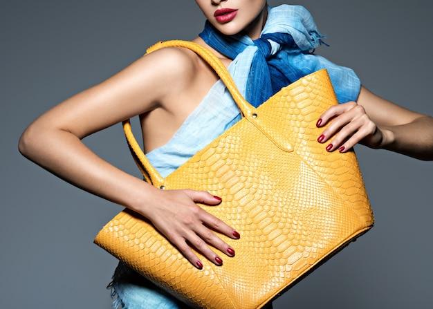 Stilvolle schöne frau, die blauen schal mit gelber handtasche trägt. model
