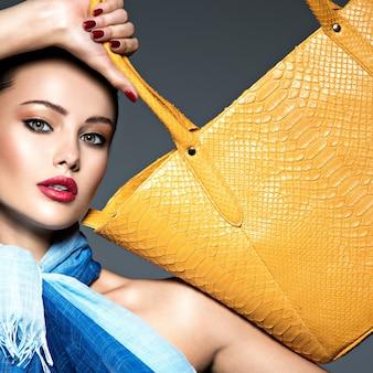 Stilvolle schöne frau, die blauen schal mit gelber handtasche trägt.