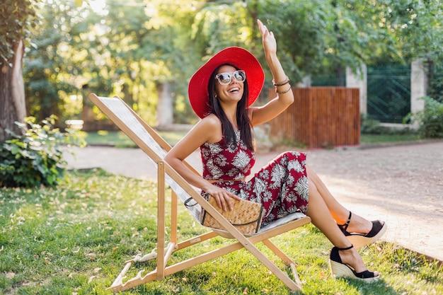 Stilvolle schöne frau, die im liegestuhl im tropischen stilausstattung sitzt, hand winkt, sommermodetrend, strohhandtasche, roter hut, sonnenbrille, accessoires, lächeln, fröhliche stimmung, urlaub