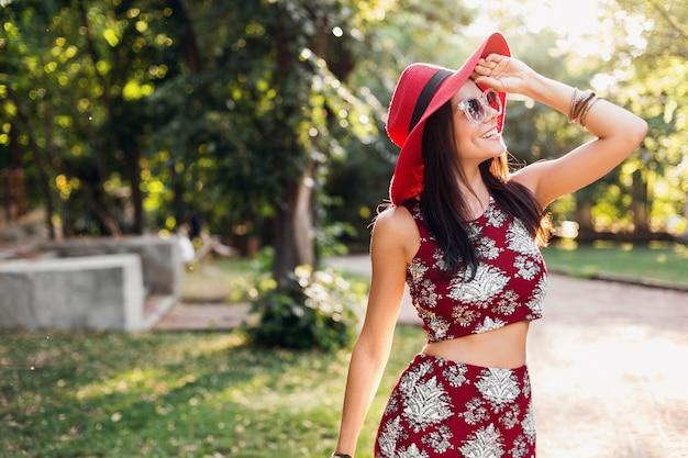 Stilvolle schöne frau, die im park im tropischen outfit geht. dame im streetstyle-sommermodetrend. trägt roten hut, sonnenbrille, accessoires. mädchen lächelt in fröhlicher stimmung im urlaub.