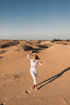 Stilvolle schöne frau, die im wüstensand geht, gekleidet in weißen hosen und bluse, die strohhut auf sonnenuntergang tragen