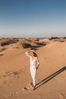 Stilvolle schöne frau, die im wüstensand im weißen outfit mit strohhut auf sonnenuntergang geht