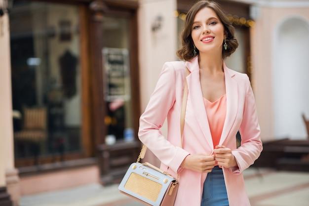 Stilvolle schöne frau gekleidet in rosa jacke mit eleganter handtasche, die in stadtstraße geht