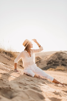 Stilvolle schöne frau im wüstensand im weißen outfit, das strohhut auf sonnenuntergang trägt