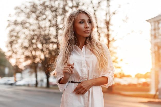 Stilvolle schöne junge frau im modischen weißen hemd geht auf der straße bei sonnenuntergang
