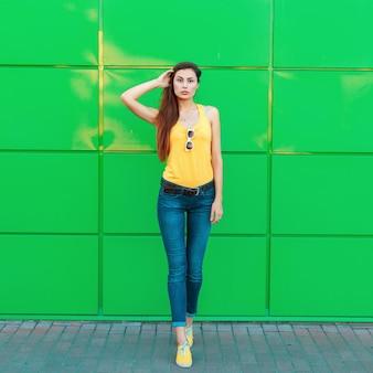 Stilvolle schöne junge frau in einem gelben t-shirt, jeans und gelben schuhen, die nahe einer hellgrünen wand aufwerfen