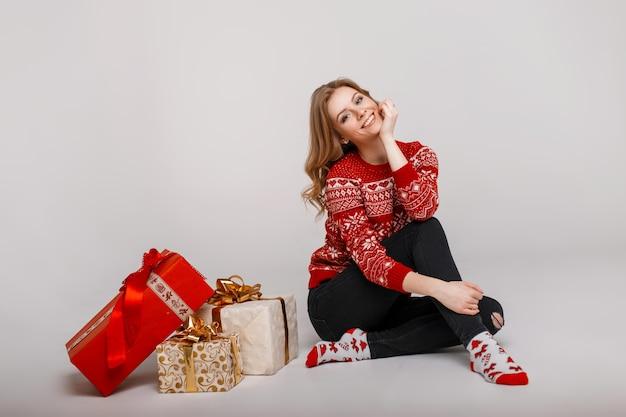 Stilvolle schöne junge frau in einem mode rot gestrickten pullover sitzt in der nähe von geschenken auf einem grauen hintergrund