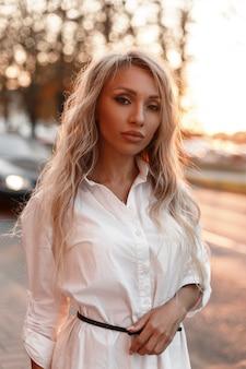 Stilvolle schöne junge modellfrau in einem weißen hemd in der stadt bei sonnenuntergang