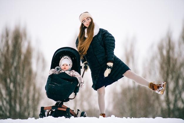 Stilvolle schöne junge mutter haben spaß zusammen mit reizendem kind, das im winter im kinderwagen draußen sitzt. glückliche fröhliche frau und kleine tochter, die im schnee spielen.