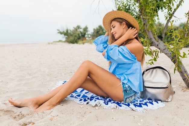 Stilvolle schöne lächelnde frau, die auf sand mit dünnen beinen in den sommerferien am tropischen strand trägt strohhut, silberner rucksack sitzt