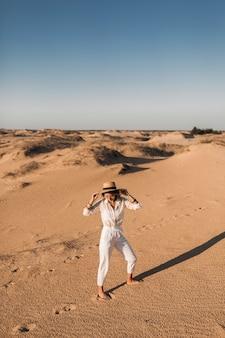 Stilvolle schöne sorglose glückliche frau, die im wüstensand geht, gekleidet in weißen hosen und bluse, die strohhut auf sonnenuntergang tragen