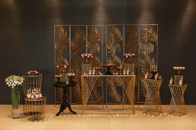 Stilvolle schokoriegel auf der geburtstags- oder hochzeitsfestparty hautnah. süßigkeiten und köstliche desserts auf einem festlichen tisch mit blumen geschmückt. set schöne kuchen auf den tellern im urlaub