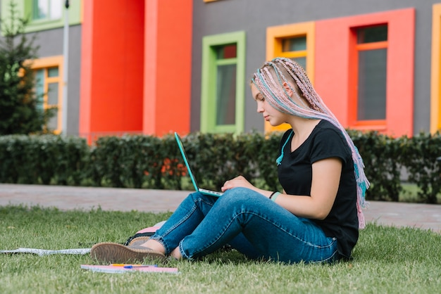 Stilvolle schulmädchen im park mit laptop