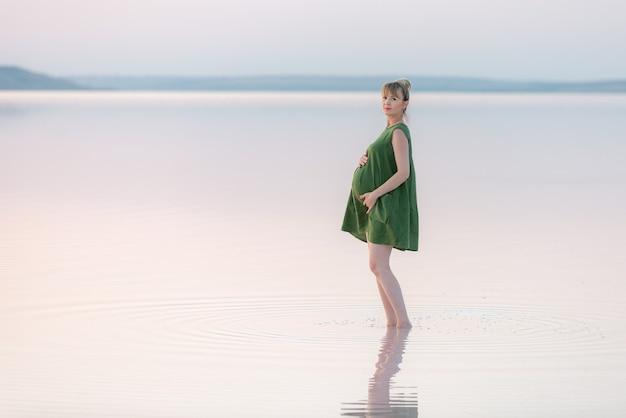 Stilvolle schwangere frau im grünen kleid, das bei sonnenuntergang aufwirft, die kamera betrachtet