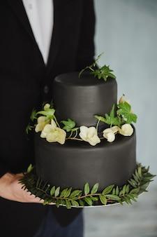 Stilvolle schwarze hochzeitstorte zu den händen des bräutigams