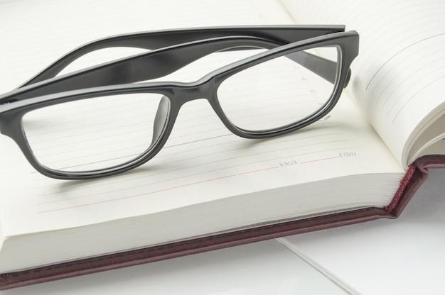 Stilvolle schwarze lesebrille auf einem offenen tagebuch, nahaufnahmebanner