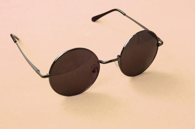 Stilvolle schwarze sonnenbrille mit runden gläsern liegt auf einer decke