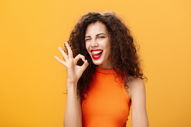 Stilvolle, selbstbewusste kaukasische freundin mit lockiger frisur, die freudig zwinkert und die zunge herausstreckt, die eine perfekte oder in ordnung zeigende geste zeigt, die sicherstellt, dass sie alles über die orangefarbene wand unter kontrolle hat.