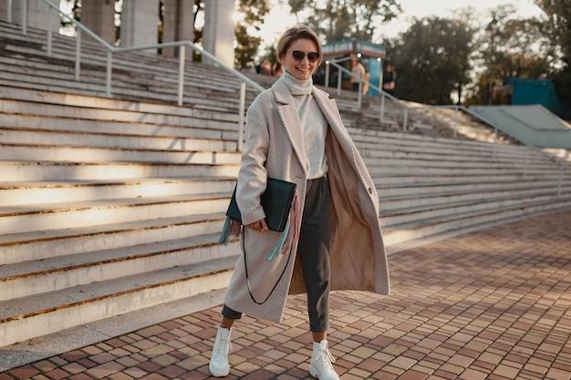 Stilvolle selbstbewusste modische frau, die in elegantem mantel auf der straße geht