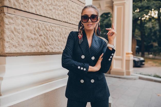 Stilvolle sexy frau gekleidet im eleganten smokinganzug, der in der stadt am sommerfrühlingstag geht