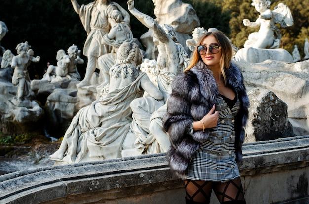 Stilvolle sexy junge frau in der sonnenbrille, im pelzmantel und im kurzen kleid, die draußen im stadtpark auf der treppe aufwerfen.