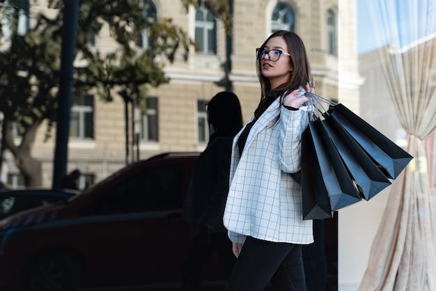 Stilvolle shopperin mit schwarzen taschen. schönes mädchen in der nähe eines modegeschäfts. konzept des schwarzen freitags.