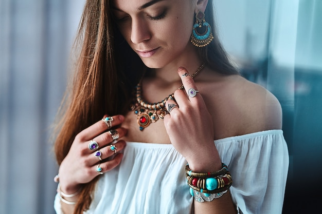 Stilvolle sinnliche boho-frau, die weiße bluse mit ohrringen, goldener halskette, armbändern und silbernen ringen mit stein trägt.