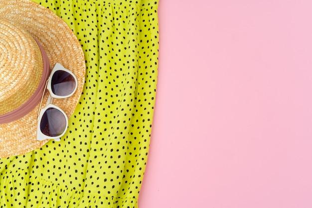 Stilvolle sommerausstattung für frau auf pastellrosahintergrund