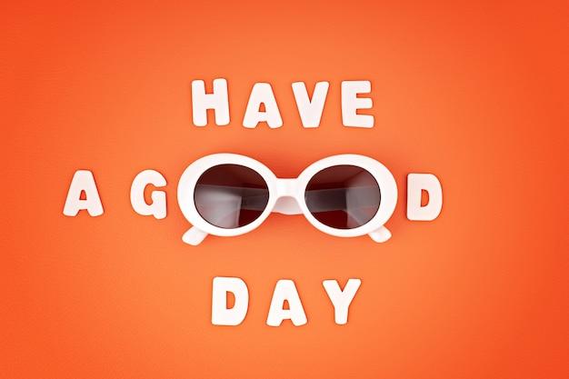 Stilvolle sonnenbrille über orange wand mit text haben sie einen guten tag. sommermode, party, sommerstil, urlaubskonzept. minimale flache lage, draufsicht