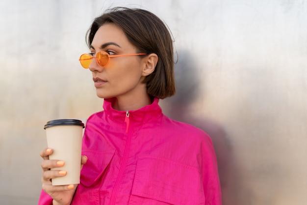 Stilvolle sportliche frau mit kurzer frisur, die mit kaffeetasse aufwirft