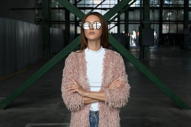 Stilvolle straße schauen oben vorbildliche lange braune haarfrau der mode in der sonnenbrille mit spiegeleffekt im rosa mantel und im weißen hemd wirft mit den händen auf, die in der industriellen speicherparkgewebeherstellung gekreuzt werden