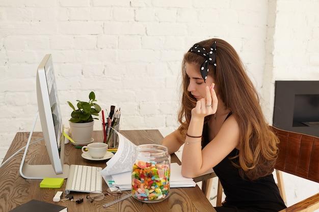 Stilvolle studentin der wirtschaftsschule, die am diplomprojekt arbeitet, an ihrem arbeitsplatz zu hause mit computer, papierbögen und inneren gegenständen auf dem tisch sitzt und süßigkeiten aus dem glas isst