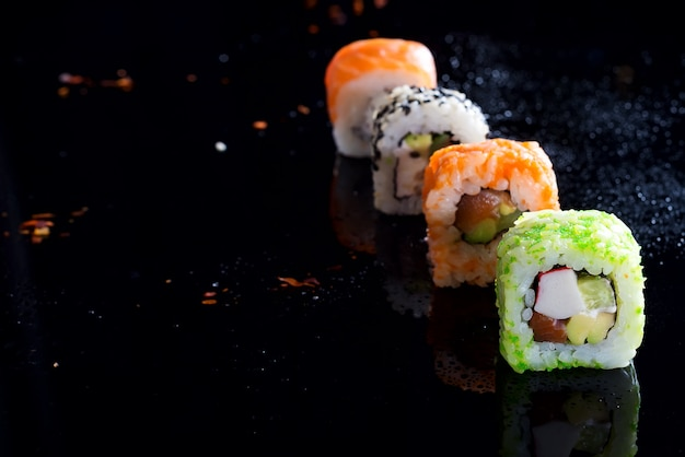 Stilvolle sushisätze auf einem schwarzen mit wassertropfen. platz kopieren