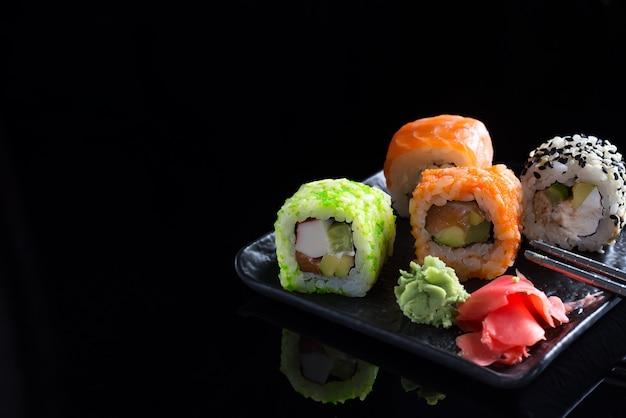 Stilvolle sushisätze auf einer schwarzen keramischen platte und chinesischen stöcken. platz kopieren