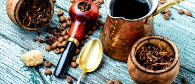 Stilvolle tabakpfeife mit tabak und gebrühtem kaffee